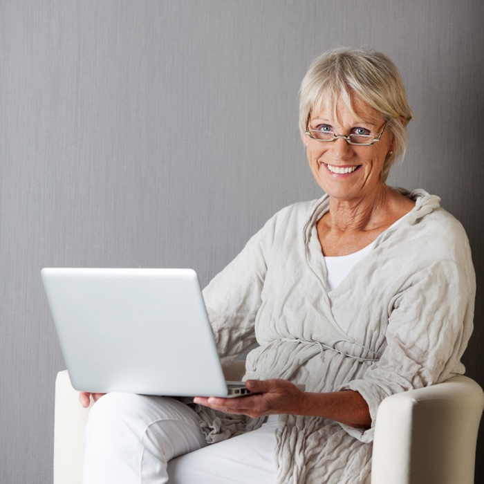 Portrait of happy senior woman with laptop sitting on couch against grey wall
