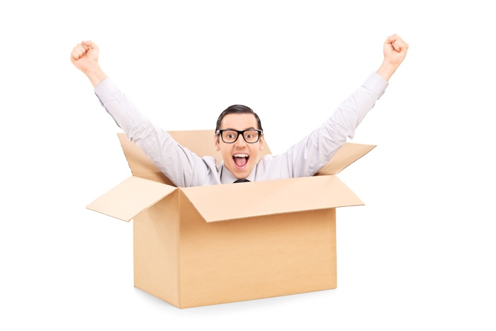 Young man gesturing happiness deep inside a box isolated on white background